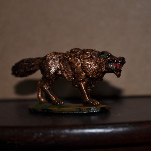 A brass colored wolf miniature with green eyes and blood-drenched teeth