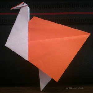 an orange and white origami bird