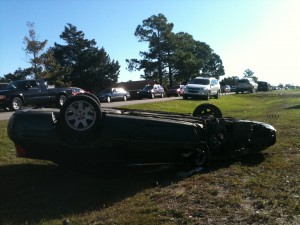 A Chrysler Sebring flipped on its roof with one wheel missing