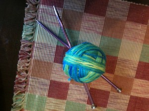 A ball of blue, green, and yellow yarn with two knitting needles crossed under it