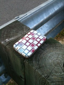 A colorful metal tin box, closed, on the wooden support beam of a bridge guardrail