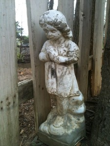 Statue of a little girl clasping her hands and looking down, next to a white picket fence