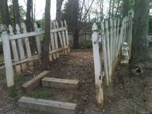 Landscaping timber steps leading up a hill, with dilapidated white picket fence and trees on either side and a small white state of a little girl clasping her hands