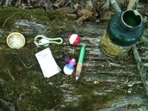 An empty bottle and cap, two fishing bobbers, a pen, a folded piece of paper, and a keychain