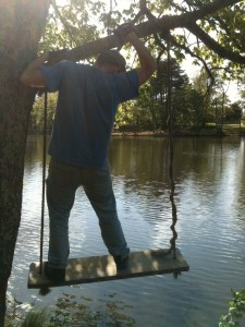 A man climbs on a tree swing by a lake